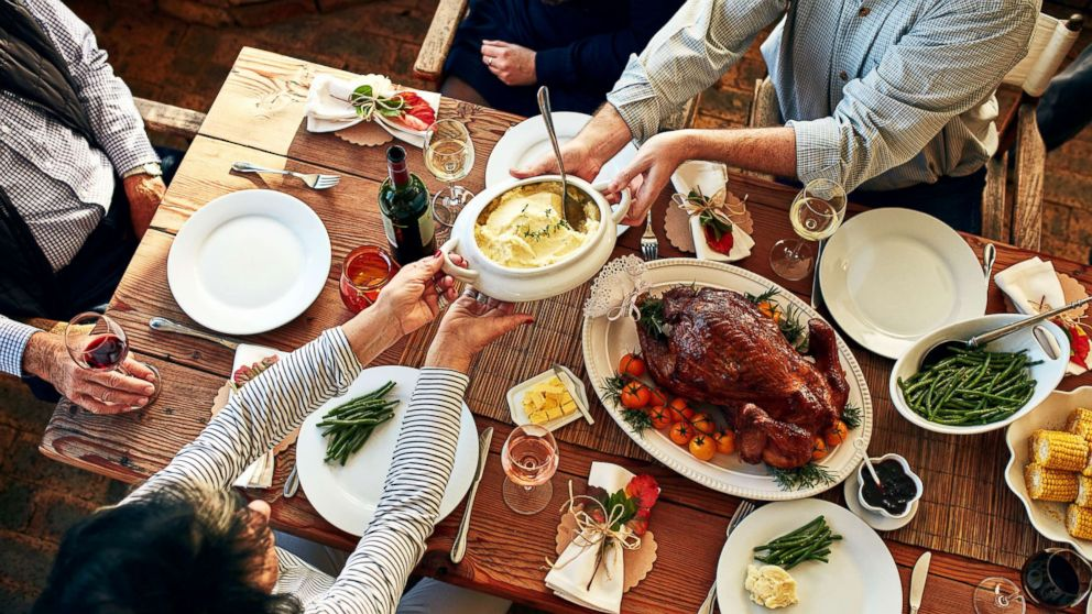 This stock photo depicts a family enjoying a Thanksgiving meal.