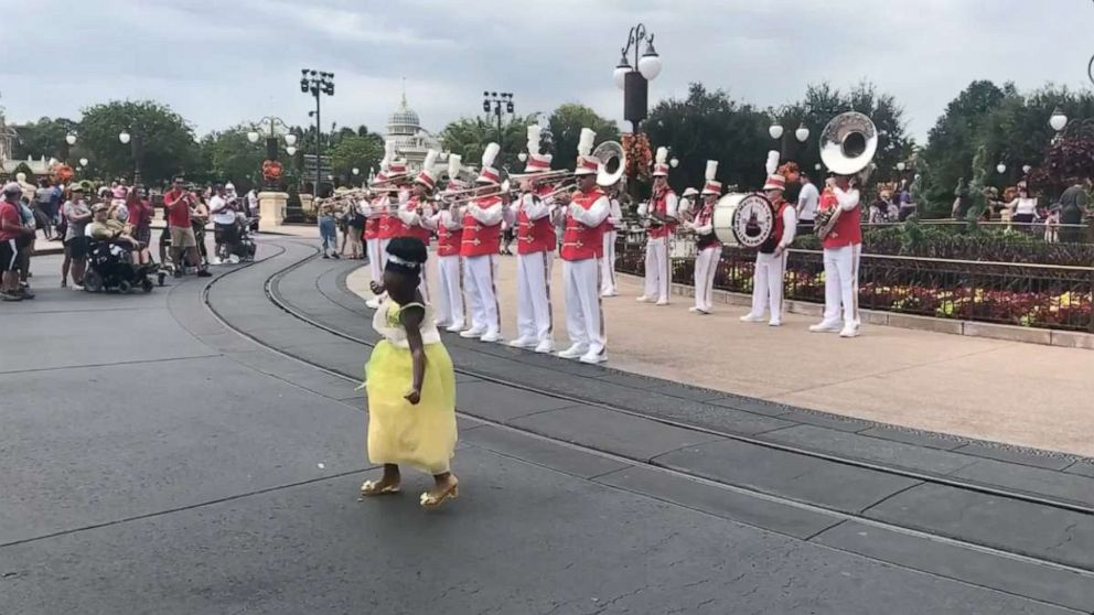 PHOTO: Sydney Elise Russell dances in the street at Walt Disney World as the Walt Disney World marching band joins in.