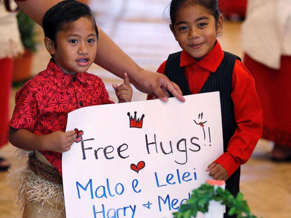 PHOTO: Children hold a placard as they await the arrival of Meghan, Duchess of Sussex and Prince Harry, Duke of Sussex for their meeting with Tonga Prime Minister in Nukualofa, Tonga, Oct. 26, 2018.