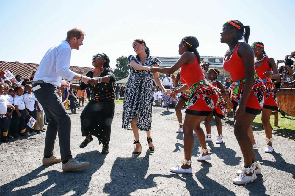 PHOTO: Prince Harry, Duke of Sussex, and Meghan, Duchess of Sussex, dance as they arrive for a visit to Justice desk, an NGO in the township of Nyanga in Cape Town, as they begin their tour of the region, Sept. 23, 2019.