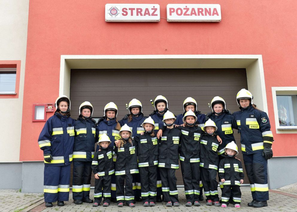 PHOTO: Girls pose with the volunteer fire department in the town of Miejsce Odrzanskie, Poland, July 31, 2019.