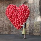 A woman hugs a bunch of balloons shaped like a heart in an undated stock photo.