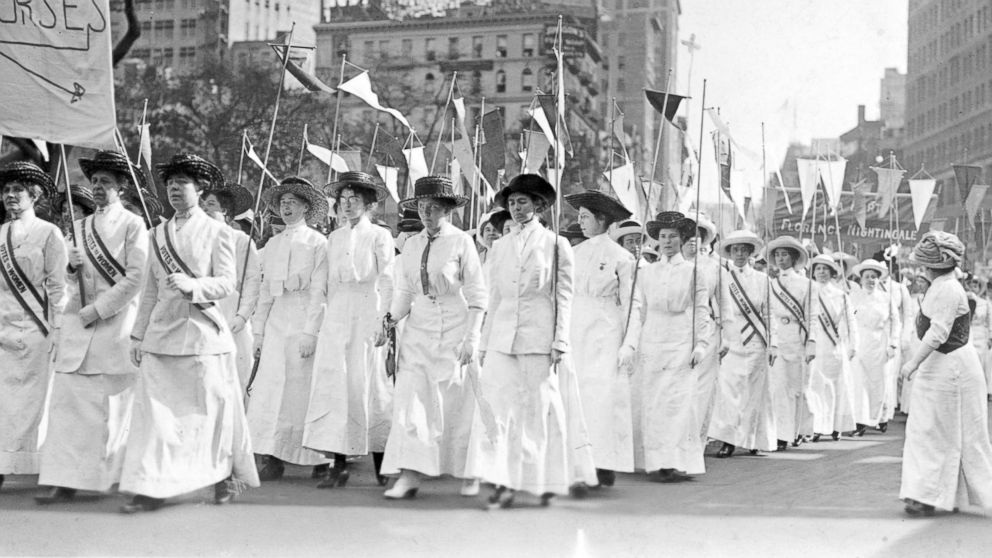 """Nurses wearing white Edwardian clothing and sashes reading, """"Votes for Women,"""" demonstrate in New York in 1913."""