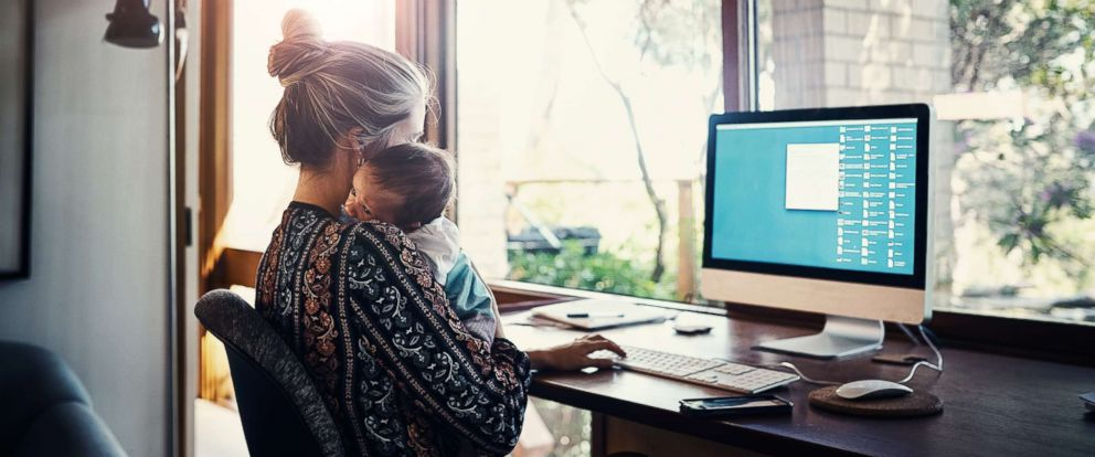 PHOTO: A working mom holds her child in this stock photo.