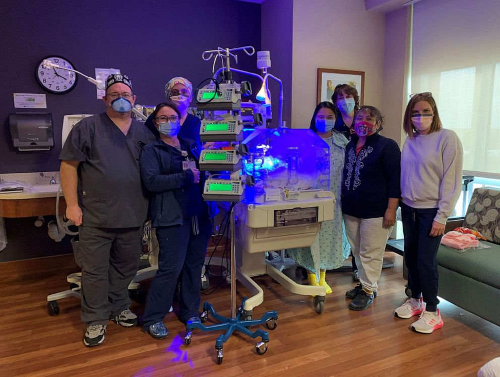 PHOTO: Kimberly Arias, wearing a hospital gown, poses with the healthcare providers at Baylor Scott and White who delivered her baby daughter Zaylynn.