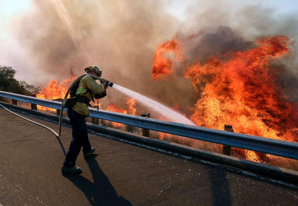 PHOTO: A firefighter battles a fire along the Ronald Reagan Freeway, aka state Highway 118, in Simi Valley, Calif., Nov. 12, 2018.