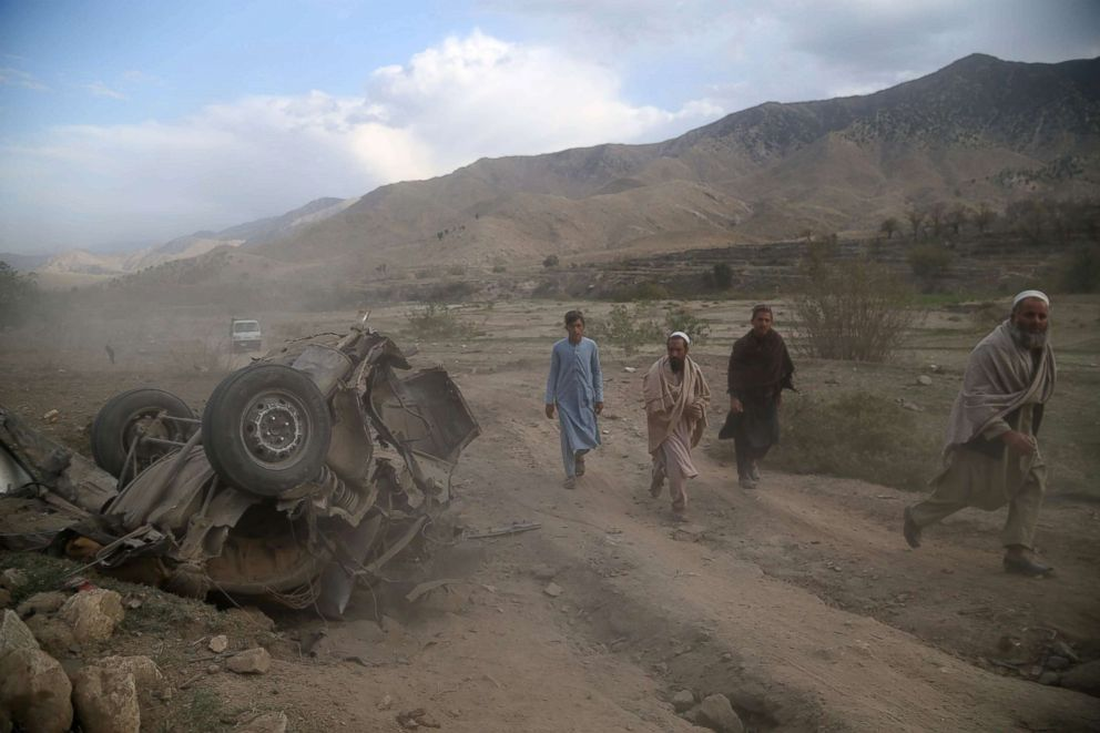 People survey the scene of a road side bomb blast in Achin district of Nangarhar province, Afghanistan, Oct. 21, 2018. At least 11 people, including children and women, from the same family were killed in the incident. No group has so far claimed responsibility for the blast, which comes on the second day of parliamentary elections in the country.