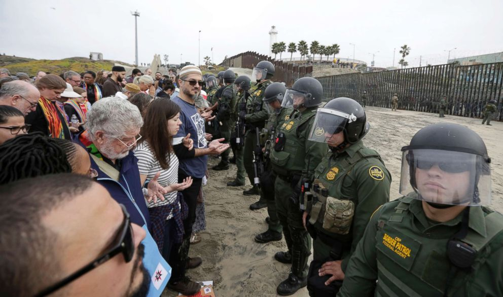 PHOTO: Immigrant rights activists stand arm in arm and line up against border patrol agents during a protest at the border wall in San Diego, Calif., Dec. 10, 2018.