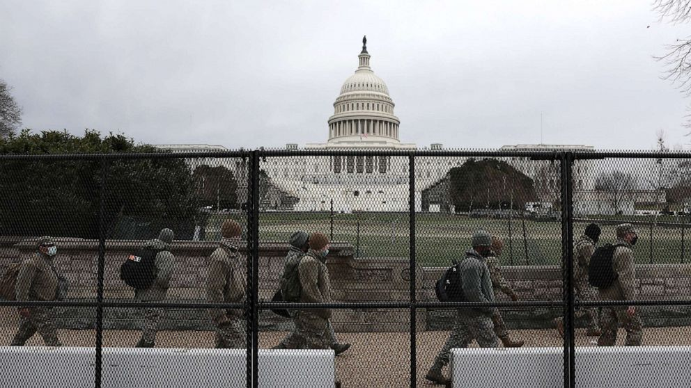 PHOTO: Members of the D.C. National Guard walk behind a fence placed around the U.S. Capitol building on Jan. 08, 2021.