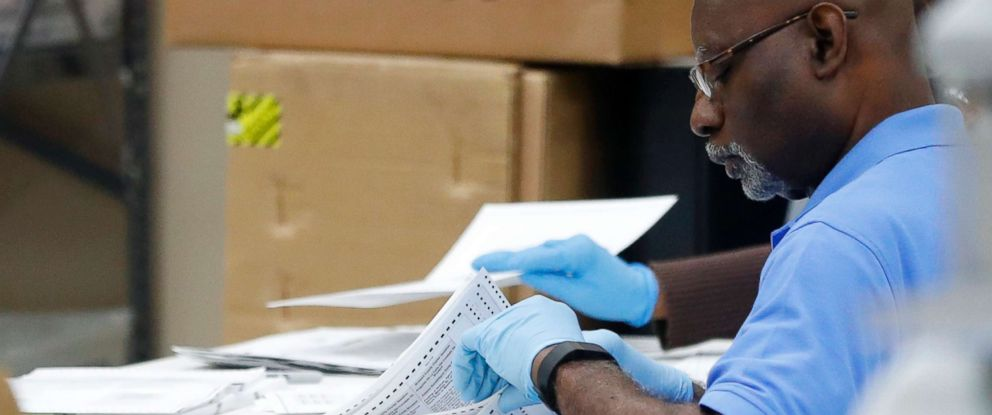 PHOTO: An employee at the Broward County Supervisor of Elections office examines ballots during a recount, Nov. 14, 2018, in Lauderhill, Fla.