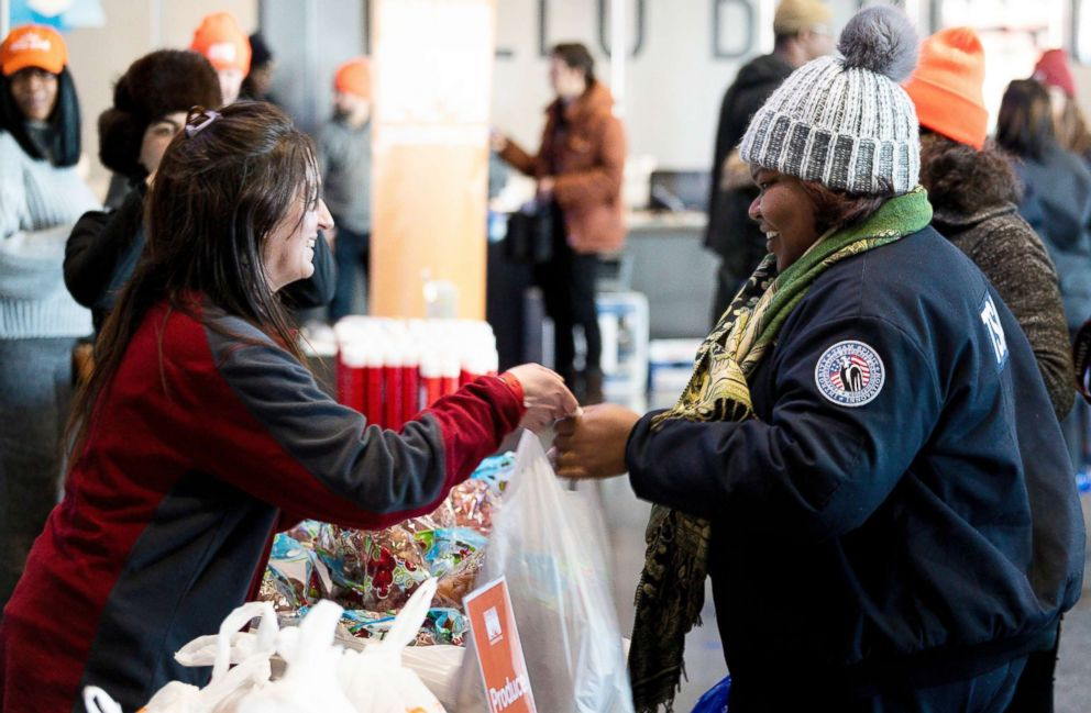 PHOTO: Amelia Williams, right, a furloughed employee of the TSA, collects goods at a food donation site set up for federal workers by the Food Bank of NYC at the Barclays Center in Brooklyn, New York, Jan. 22, 2019.