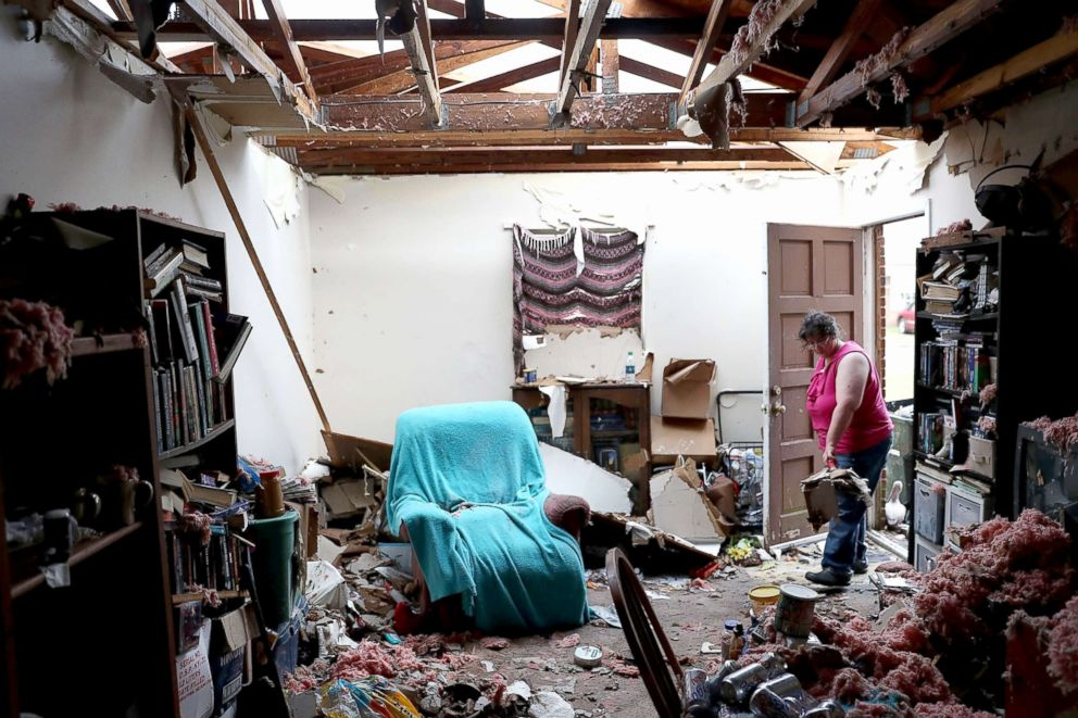 PHOTO: Amanda Logsdon begins the process of trying to clean up her home after the roof was blown off by the passing winds of Hurricane Michael, Oct. 11, 2018, in Panama City, Florida.