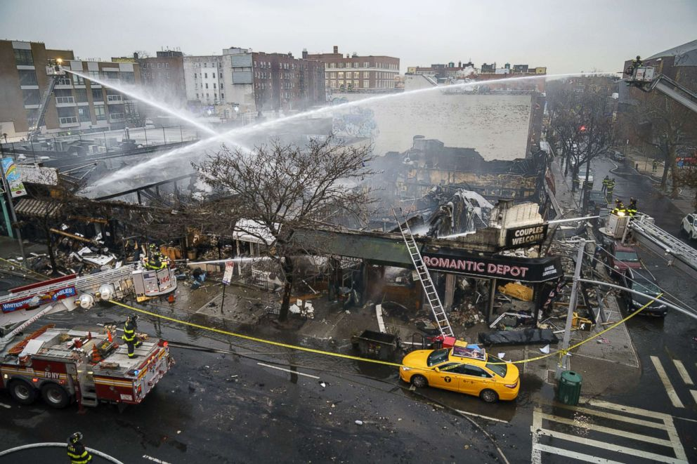 Firefighters work to put out the smoldering remains of an overnight fire that engulfed six businesses on Queens Boulevard, Dec. 13, 2018, in Queens, New York.