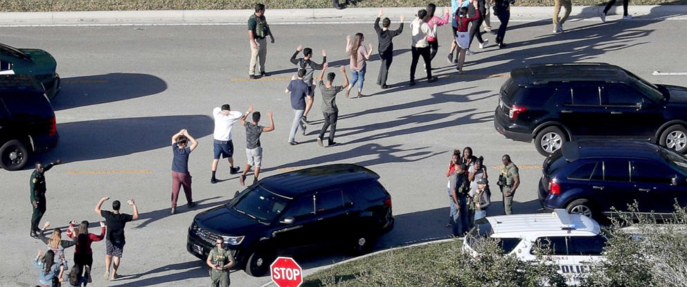 PHOTO: Students hold their hands in the air as they are evacuated by police from Marjory Stoneman Douglas High School in Parkland, Fla., after a shooter opened fire on the campus, Feb 14, 2018.