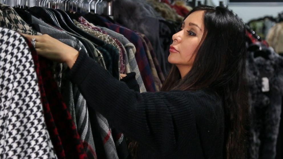 PHOTO: Nicole Polizzi organizing clothing racks in The Snooki Shop.