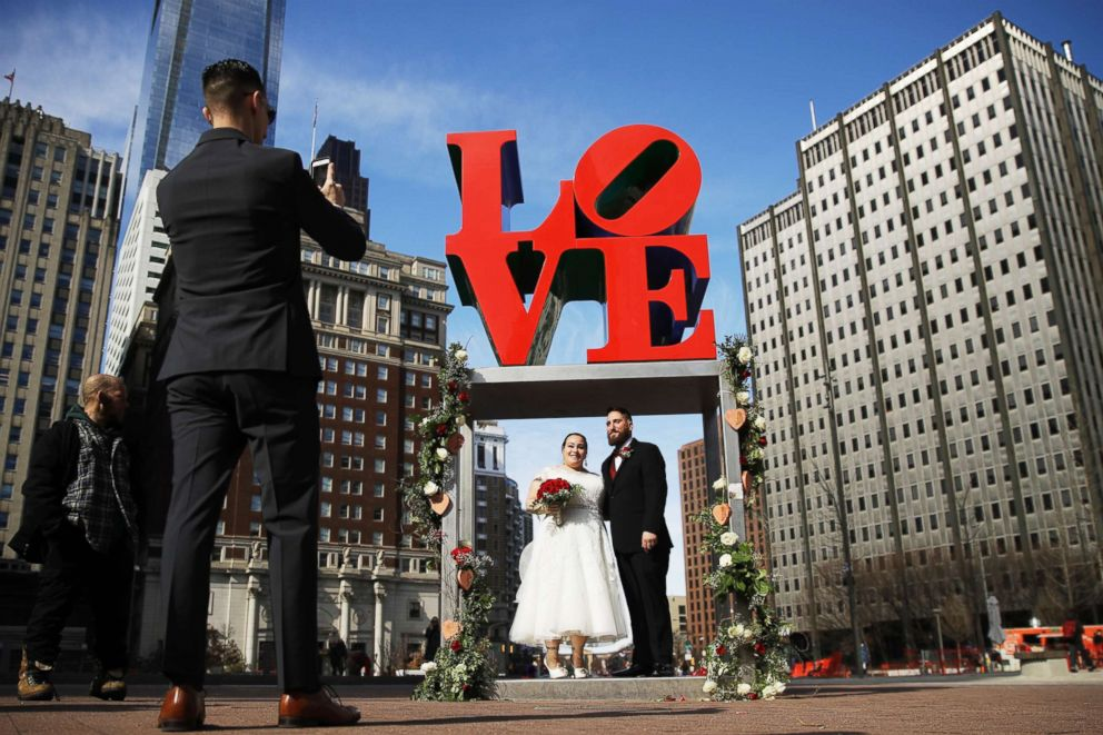 PHOTO: Newlyweds Jennifer and Paul Raffa pose for a photograph with the Robert Indiana sculpture LOVE at John F. Kennedy Plaza in Philadelphia, Feb. 14, 2019.