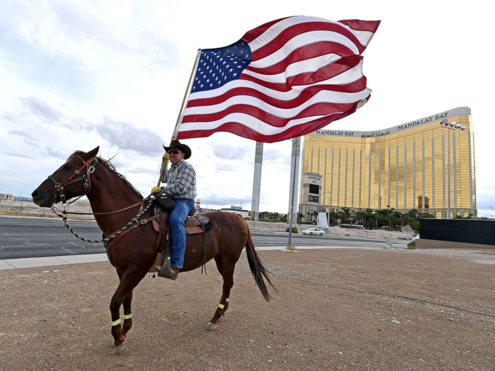 PHOTO: Rafael Sarabia holds an American flag as he rides his horse Red Sonja outside the Las Vegas Village across from Mandalay Bay Resort and Casino as a tribute to those killed in last years massacre at the site, Oct. 1, 2018, in Las Vegas, Nevada.