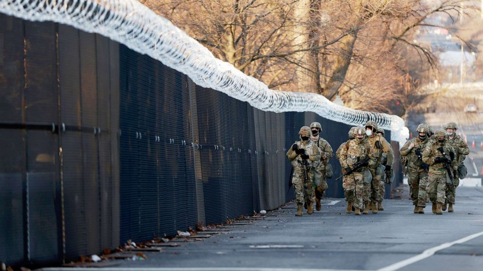 PHOTO: A group of Virginia National Guard patrol around the razor wire fence surrounding the U.S. Capitol grounds in Washington, Jan. 16, 2021.