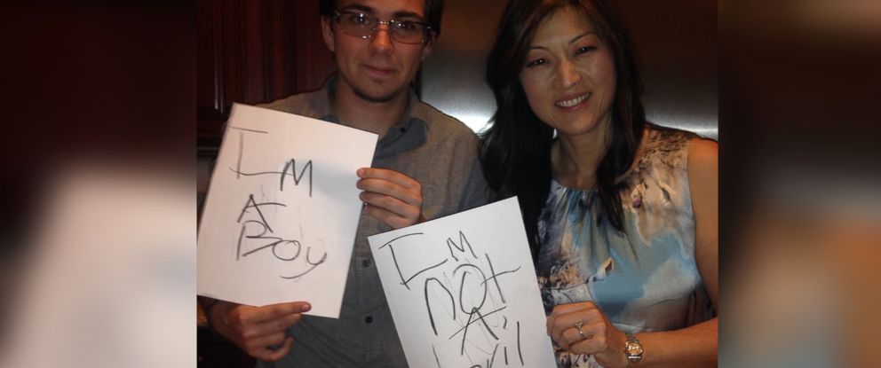 ABC News Juju Chang and Nathan Jones, who was born a female, hold signs Jones wrote when he was in the second grade.