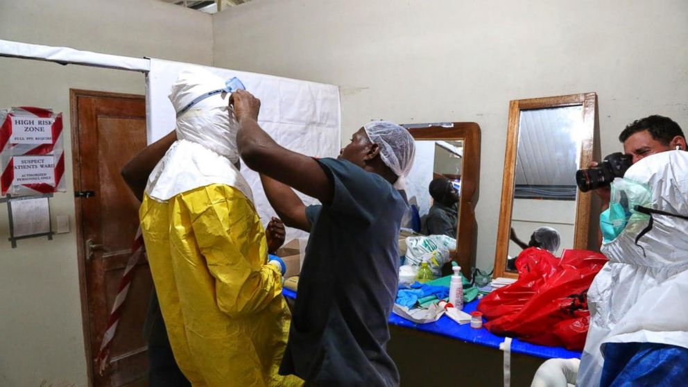 Three people help Dr. Besser put on protective gear outside the ELWA Ebola Isolation Unit in Monrovia, Liberia.