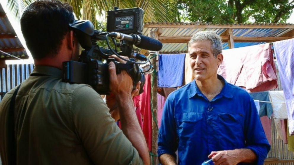 Dr. Besser stands in front of the camera outside the Ebola ward in Monrovia.
