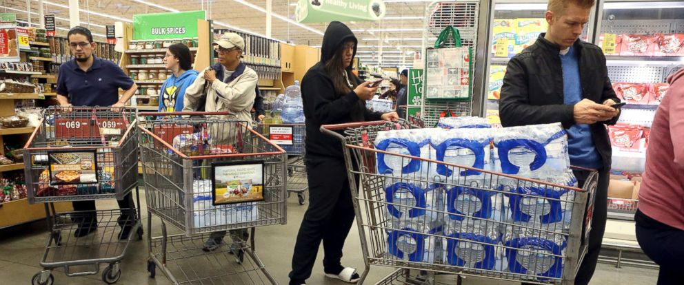 PHOTO: Customers stand in line to pay for cases of water at an H-E-B store, Dec. 15, 2016, in Corpus Christi, Texas.