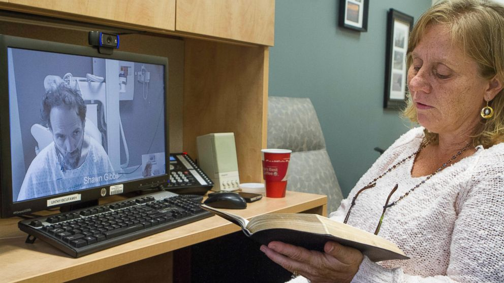 In this Sept. 10, 2014 photo released by the Nebraska Medical Center, Debbie Sacra reads Bible verses to her husband Dr. Richard Sacra via a video link in Omaha, Neb.