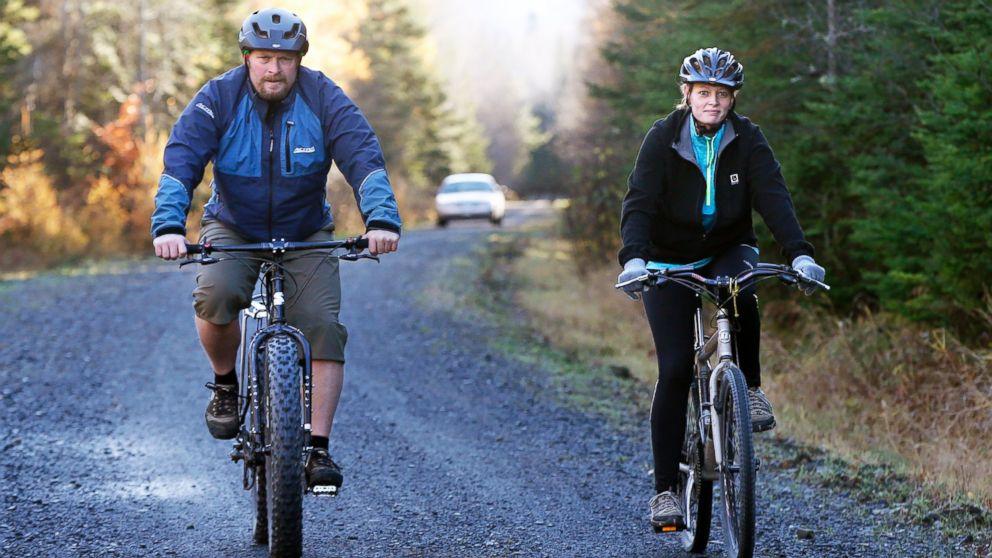 Nurse Kaci Hickox, right, and her boyfriend, Ted Wilbur are followed by a Maine State Trooper as they ride bikes on a trail near her home in Fort Kent, Maine, Oct. 30, 2014.