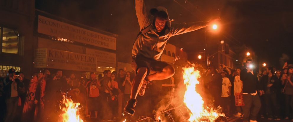 PHOTO: A man jumps over some debris that has been set on fire in the Mission district after the San Francisco Giants beat the Kansas City Royals to win the World Series on Oct. 29, 2014, in San Francisco.