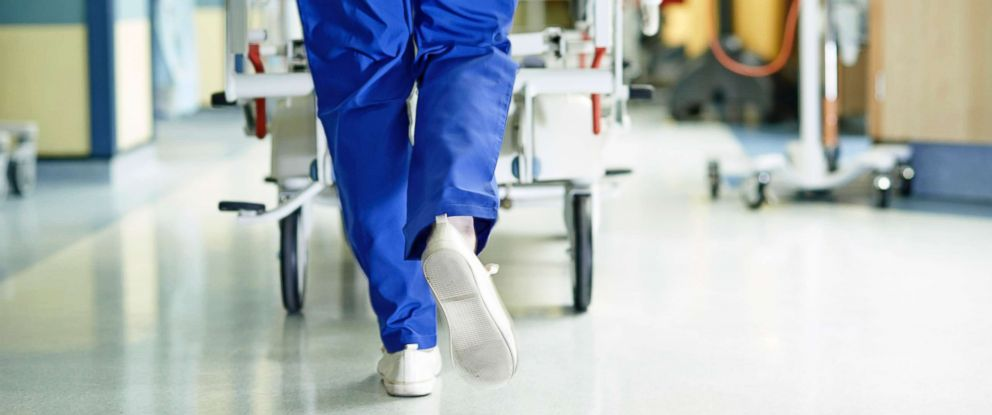 PHOTO: A medic runs with a gurney along a hospital corridor.