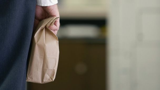 PHOTO: A businessman carries a paper lunch bag.