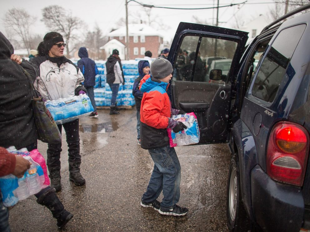 PHOTO: Volunteers load cases of free water into waiting vehicles at a water distribution centre at Salem Lutheran Church in Flint, Mich., on March 5, 2016.