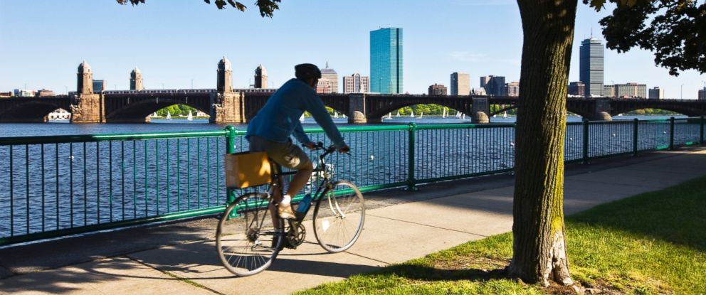 PHOTO: A man bikes along the Charles River in Boston.