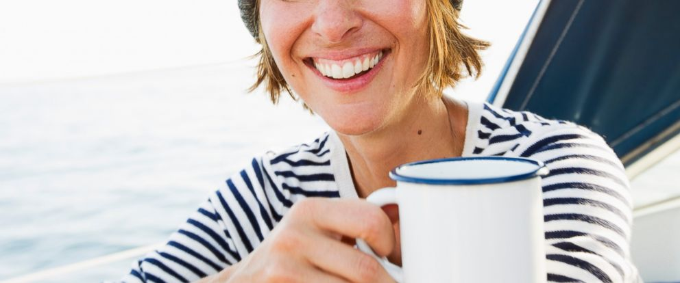 PHOTO: A woman is pictured smiling, while drinking coffee.
