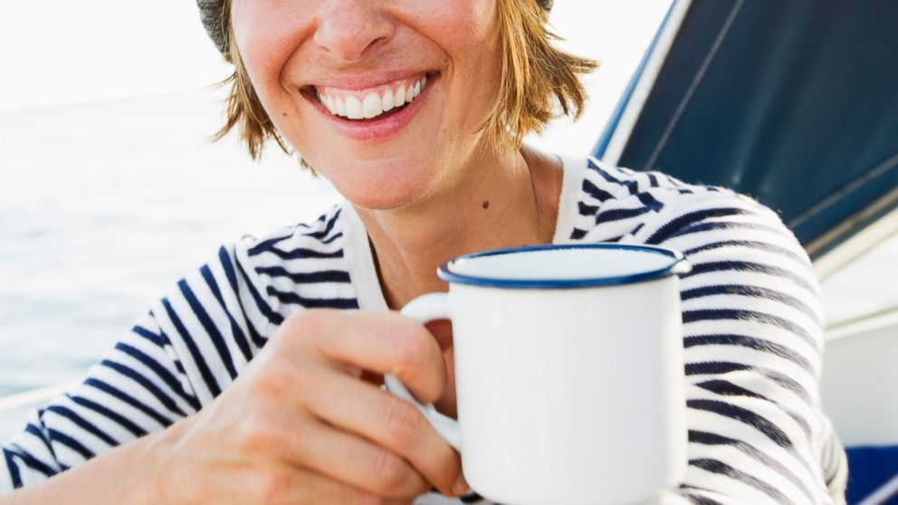 A woman is pictured smiling, while drinking coffee.