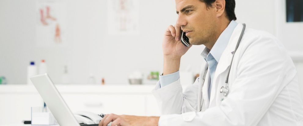 PHOTO: Doctor talks on the phone call while using a laptop computer in this stock photo.
