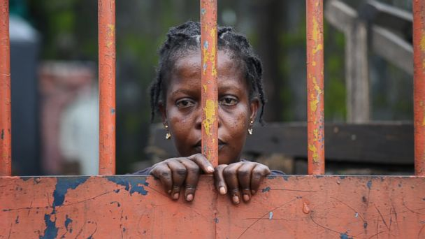 PHOTO: A West Point slum resident looks from behind closed gates