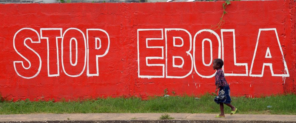 "PHOTO: A girl walks past a painted wall reading ""Stop Ebola"" in Monrovia, Liberia on Aug. 31, 2014."