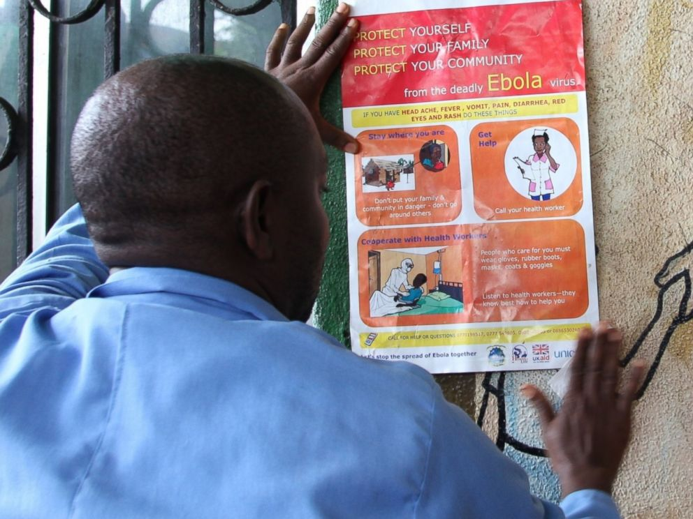 PHOTO: A nurse sets an information sign about Ebola on a wall of a public health center