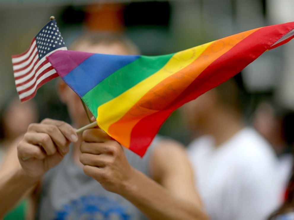 PHOTO: A protester holds an American flag and rainbow flag in front of the Miami-Dade Courthouse to show his support of the LGBTQ couples, July 2, 2014, in Miami.