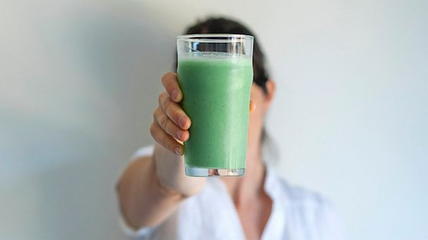 PHOTO: Woman holding up glass of fresh vegetable juice.