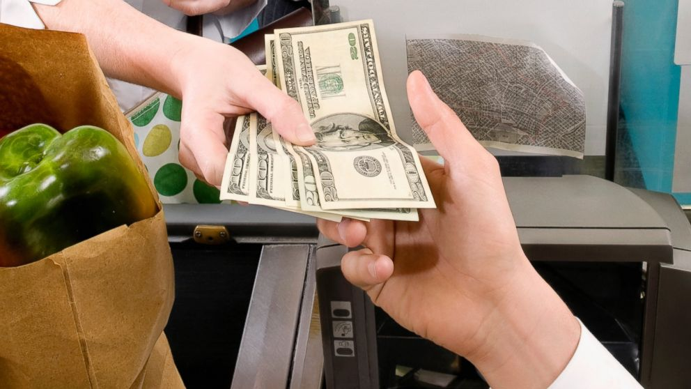 A Customer Is Pictured Handing Cashier Money In This Stock Image