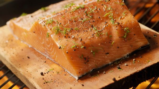 PHOTO: A plank salmon fillets on an outdoor BBQ is seen.