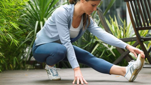 PHOTO: In this stock photo, a woman wearing running clothes is pictured stretching.