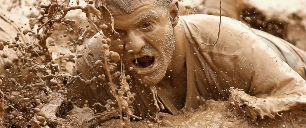 PHOTO: A competitor crawls through mud during Toughmudder at Phillip Island Grand Prix Circuit, March 23, 2014 in Phillip Island, Australia.