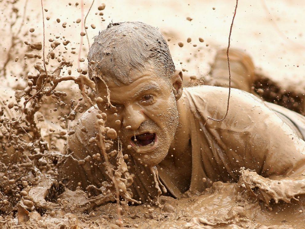 PHOTO: A competitor crawls through mud during Toughmudder at Phillip Island Grand Prix Circuit, March 23, 2014 in Phillip Island, Australia.