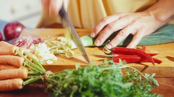 PHOTO: A woman chops a leek on a cutting board