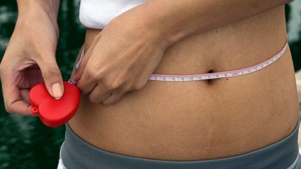 PHOTO: A woman measures her waistline using a tape measure.