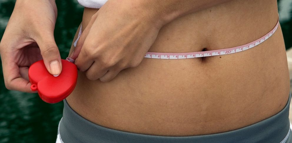 PHOTO: A woman measures her waistline using a tape measure.