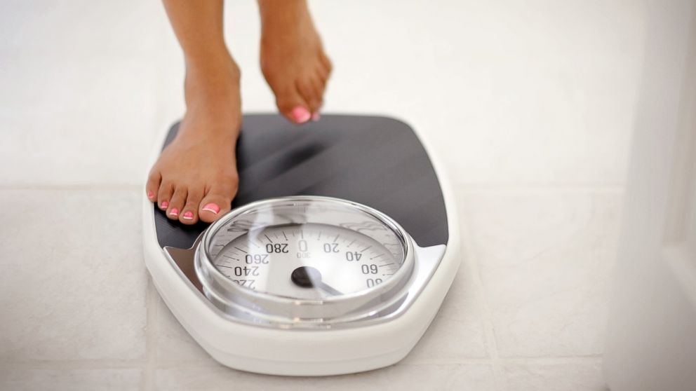 A woman stands on a bathroom scale in this undated stock photo.